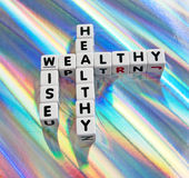 Healthy, wealthy and wise. Text ' healthy ', ' wealthy ' and ' wise ' inscribed on small white cubes in black uppercase letters and arranged crossword style with Royalty Free Stock Photography