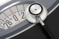 Healthy Weight. Close up of stethoscope on a weight scales stock photos