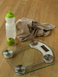 Healthy weight loss. Shown through water bottle, exersize towel, fresh apple and bathroom scale Stock Photography