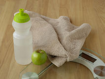 Healthy weight loss. Shown through water bottle, exersize towel, fresh apple and bathroom scale Stock Photos
