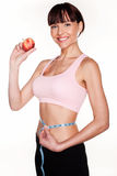 Healthy Weightloss Concept. A happy smiling young woman holds up an apple while measuring her waist with the other hand in a healthy weightloss concept Stock Image