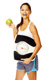 Healthy weightloss woman. Portrait of a slim fitness woman with apple and scale promoting healthy weightloss Royalty Free Stock Photography