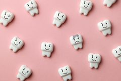 Healthy white teeth are smiling and tooth with caries is sad on pink background. stock photos