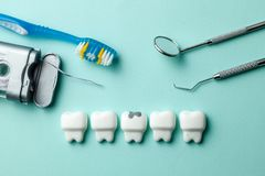 Healthy white teeth and tooth with caries on green mint background. Toothbrush floss and dentist tools mirror, hook. royalty free stock photography