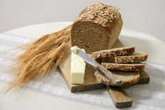 Healthy whole grain bread with butter. Whole grain bread cut and ready for butter with stalks of wheat on a cutting board, set on a table cloth royalty free stock photography