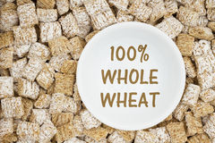 Healthy whole grain cereal. 100% whole wheat text with whole grain wheat cereal with a white bowl Stock Images