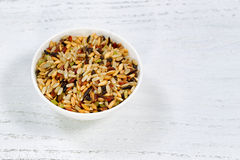 Healthy whole grains of raw rice in bowl ready to cook. Close up of several whole grains of rice in bowl on white wood stock photos
