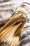 Healthy wholewheat Italian spaghetti pasta. In a glass jar with the colors of the Italian national flag lying on its side on a rustic wooden surface in sunshine Royalty Free Stock Photography
