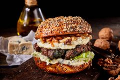 Healthy wholewheat walnut and cheese burger. With a thick beef patty ob a rustic wood table with ingredients Royalty Free Stock Photo