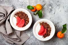 Healthy winter breakfast. Greek yogurt bowl with chocolate gingerbread granola and grapefruit. Top view, flat lay, overhead. stock photo