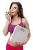 Healthy woman with an apple and scales. Royalty Free Stock Photos