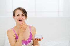 Healthy woman applying creme on face in bedroom Royalty Free Stock Images