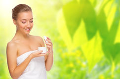 Healthy woman with bady cream on spring background Stock Images