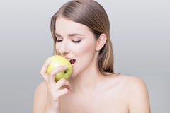 Healthy woman. Beautiful girl eating a green apple isolated on white background Royalty Free Stock Image