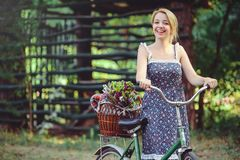 A healthy woman. Beauty Summer model girl with bright colors bicycle forest and basket. style leisure. A beautiful lady with blond royalty free stock image