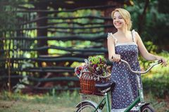 A healthy woman. Beauty Summer model girl with bright colors bicycle forest and basket. style leisure. A beautiful lady with blond stock image