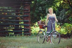 A healthy woman. Beauty Summer model girl with bright colors bicycle forest and basket. style leisure. A beautiful lady with blond royalty free stock photo
