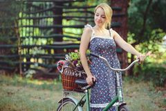 A healthy woman. Beauty Summer model girl with bright colors bicycle forest and basket. style leisure. A beautiful lady with blond stock photo
