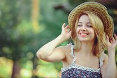 A healthy woman. Beauty Summer model girl with bright flowers happy forest. style leisure. A beautiful white lady in a straw hat. Stock Photos
