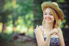 A healthy woman. Beauty Summer model girl with bright flowers happy forest. style leisure. A beautiful white lady in a straw hat. Stock Images
