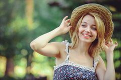 A healthy woman. Beauty Summer model girl with bright flowers happy forest. style leisure. A beautiful white lady in a straw hat. Royalty Free Stock Image