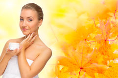 Healthy woman with body cream on autumnal background Stock Photo