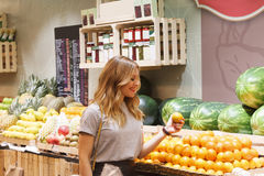 Healthy woman buying oranges on the fruit market Royalty Free Stock Photo
