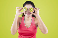 Healthy woman close her eyes with slice of kiwi Stock Photos