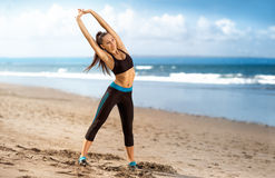 Healthy woman doing exercising on the beach Stock Photos