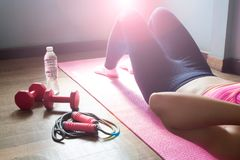 Healthy woman doing sit-ups with sport equipments and water, wor Royalty Free Stock Images