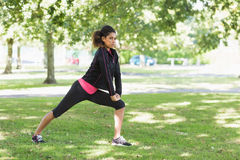 Healthy woman doing stretching exercise in park Stock Image