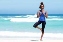 Healthy woman doing yoga exercise at beach Stock Image