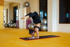 Healthy woman doing yoga and exercises stretched. In yellow studio royalty free stock photo