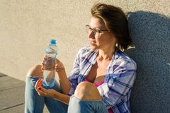 Healthy woman drinks water from bottle. Outdoor. Adult healthy woman drinks water from bottle. Outdoor Royalty Free Stock Photography