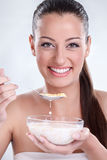 Healthy woman eating cornflakes cereals. Beautiful healthy woman eating cornflakes and showing her bowl with milk and cereals Royalty Free Stock Photography