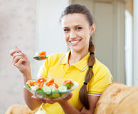 Healthy woman eating  salad on sofa Stock Images