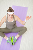 Healthy woman on fitness mat meditating Stock Image