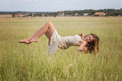 Healthy woman floating in nature meadow Royalty Free Stock Photo