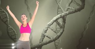 Healthy woman with hands raised against DNA structures Stock Photo