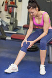 Healthy woman with an injured knee sitting in gym Stock Images