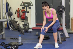 Healthy woman with an injured knee sitting in gym Royalty Free Stock Image