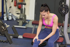 Healthy woman with an injured knee sitting in gym Stock Photography