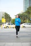 Healthy woman jogging in city Stock Photos