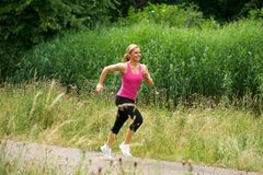 Healthy woman jogging in the park on a summer day Stock Photos