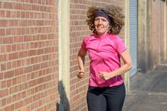Healthy woman jogging in town on the sidewalk stock photography