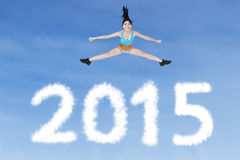Healthy woman jumping over numbers 2015 Stock Images