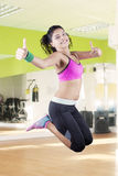 Healthy woman jumping and showing thumbs up Stock Photography