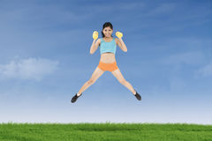 Healthy woman leaps with dumbbells Royalty Free Stock Image