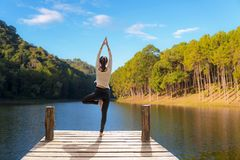 Healthy woman lifestyle balanced practicing meditate and zen energy yoga on the bridge in morning stock photos
