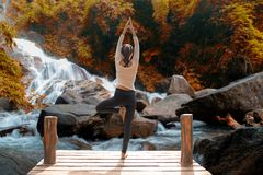 Healthy woman lifestyle balanced practicing meditate and zen energy yoga on the bridge in morning the autumn waterfall in nature. royalty free stock images
